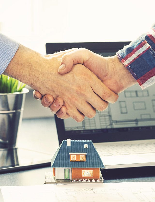 real estate agent shaking hands with customer after deal at office